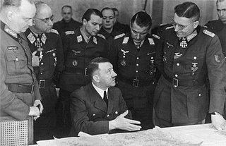 Hitler im März 1945 an der Ostfront in einer Lagebesprechung. Er war gezeichnet von seiner Parkinson-Krankheit und konnte nicht mehr länger als eine halbe Stunde stehen; die zitternde linke Hand ist unter dem Kartentisch verborgen. Neumann&Eberle: «Seine geistigen Fähigkeiten wurden durch die Krankheit nicht beeinträchtigt.»