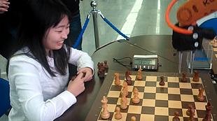 Jeden Zug des Greifarmes mit einem Lächeln quittiert und dann doch verloren: Ju Wenjun an einer Rahmenveranstaltung der WM 2015 in Sochi bei einer Blitzpartie gegen den Roboter